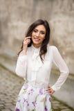 Giovane donna felice che comunica sul telefono mobile Immagini Stock