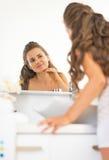 Giovane donna felice che controlla condizione della pelle facciale Immagini Stock