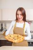 Giovane donna felice che cucina pizza Fotografie Stock Libere da Diritti