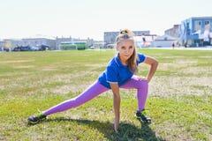 Giovane donna felice che fa allungando allenamento all'aperto Immagine Stock