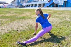 Giovane donna felice che fa allungando allenamento all'aperto, vista posteriore Immagine Stock Libera da Diritti