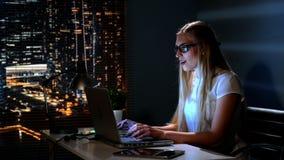 Giovane donna felice che fa tardi acquisto proficuo nel negozio di Internet alla notte video d archivio