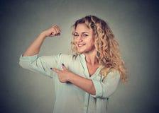 Giovane donna felice che flette i muscoli gli che mostrano forza fotografie stock