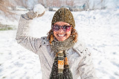 Giovane donna felice che gioca lotta della palla di neve fotografie stock libere da diritti