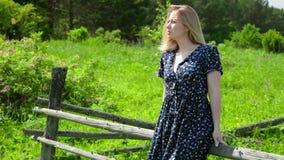 Giovane donna felice che gode del sole che si siede sul recinto di legno sulla natura della campagna sopra erba verde piacevole stock footage
