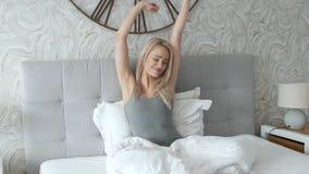 Giovane donna felice che gode della mattina soleggiata sul letto stock footage