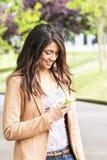 Giovane donna felice che guarda messaggio su movile. Fotografia Stock Libera da Diritti