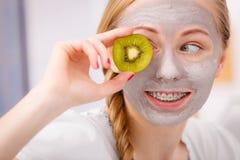 Giovane donna felice che ha kiwi della tenuta della maschera di protezione Immagini Stock