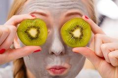 Giovane donna felice che ha kiwi della tenuta della maschera di protezione Fotografie Stock Libere da Diritti