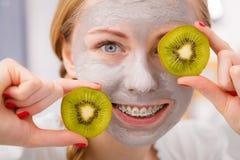 Giovane donna felice che ha kiwi della tenuta della maschera di protezione Immagine Stock