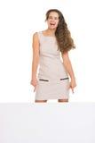 Giovane donna felice che indica giù sul tabellone per le affissioni in bianco Immagine Stock