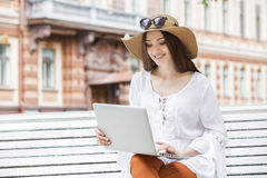 Giovane donna felice che lavora con un computer portatile che si siede su un banco Immagine Stock