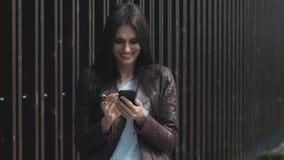 Giovane donna felice che manda un sms sullo smartphone nella città stock footage