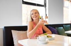 Giovane donna felice che mangia pranzo al ristorante fotografia stock libera da diritti