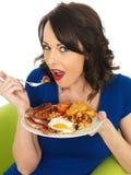 Giovane donna felice che mangia una prima colazione inglese piena Immagini Stock Libere da Diritti