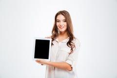 Giovane donna felice che mostra lo schermo di computer in bianco della compressa Fotografia Stock Libera da Diritti