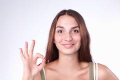 Giovane donna felice che mostra segno giusto con le dita Immagini Stock