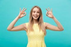 Giovane donna felice che mostra segno giusto con le dita con il grande sorriso isolate su un fondo blu Fotografia Stock Libera da Diritti