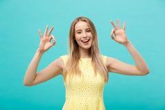 Giovane donna felice che mostra segno giusto con le dita con il grande sorriso isolate su un fondo blu Immagini Stock