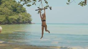 Giovane donna felice che oscilla sulla corda alla bella spiaggia archivi video