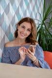 Giovane donna felice che parla sul telefono cellulare con l'amico mentre sedendosi da solo nell'interno moderno della caffetteria immagini stock libere da diritti