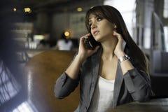 Giovane donna felice che parla sul telefono in una caffetteria Fotografia Stock