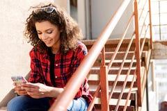 Giovane donna felice che per mezzo del cellulare sulla scala Immagini Stock