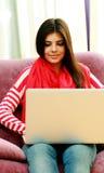 Giovane donna felice che per mezzo del computer portatile Immagini Stock Libere da Diritti