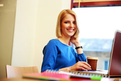 Giovane donna felice che per mezzo del computer portatile Fotografia Stock Libera da Diritti