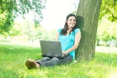 Giovane donna felice che per mezzo del computer portatile all'aperto Immagini Stock