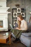 Giovane donna felice che per mezzo del computer portatile e praticando il surfing il web Fotografia Stock