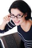 Giovane donna felice che per mezzo del suo computer portatile Immagine Stock Libera da Diritti