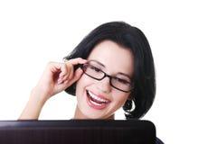 Giovane donna felice che per mezzo del suo computer portatile Immagini Stock Libere da Diritti