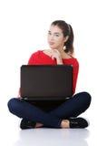 Giovane donna felice che per mezzo del suo computer portatile Fotografie Stock Libere da Diritti