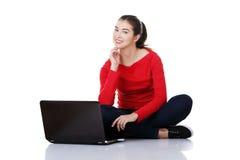 Giovane donna felice che per mezzo del suo computer portatile Fotografie Stock