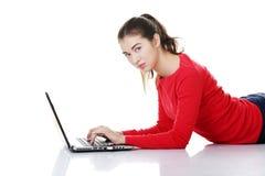 Giovane donna felice che per mezzo del suo computer portatile. Immagine Stock Libera da Diritti