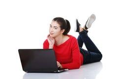 Giovane donna felice che per mezzo del suo computer portatile. Immagini Stock Libere da Diritti