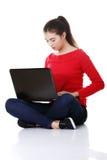 Giovane donna felice che per mezzo del suo computer portatile Immagini Stock
