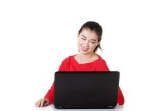 Giovane donna felice che per mezzo del suo computer portatile. Fotografie Stock Libere da Diritti