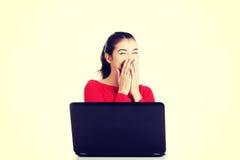 Giovane donna felice che per mezzo del suo computer portatile Fotografia Stock