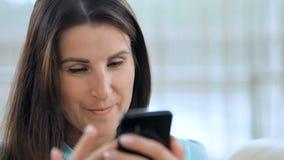 Giovane donna felice che per mezzo del suo smartphone sullo strato all'interno stock footage