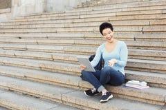 Giovane donna felice che per mezzo della compressa digitale all'aperto Immagine Stock