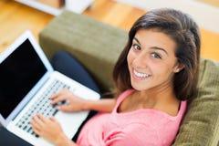 Giovane donna felice che per mezzo di un computer portatile immagine stock libera da diritti