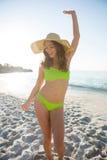 Giovane donna felice che porta bikini verde mentre ballando alla spiaggia Fotografie Stock