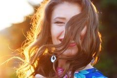 Giovane donna felice che posa nel parco contro il tramonto fotografie stock libere da diritti