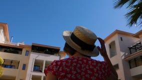 Giovane donna felice che posa vestito e gli occhiali da sole rossi d'uso La macchina fotografica fila intorno la posa della donna archivi video