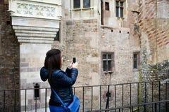 Giovane donna felice che prende un selfie al castello di Corvin, Romania Immagini Stock
