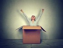 Giovane donna felice che proveniente fuori da una piccola scatola immagini stock libere da diritti