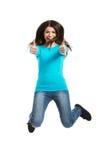 Giovane donna felice che salta con i pollici su Immagine Stock