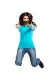 Giovane donna felice che salta con i pollici su Fotografia Stock